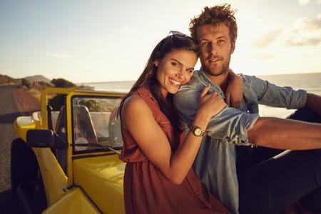 Vrolijke jonge paar zittend op de motorkap van de auto, terwijl op een roadtrip. Mooie jonge koppel samen op vakantie, buitenshuis.
