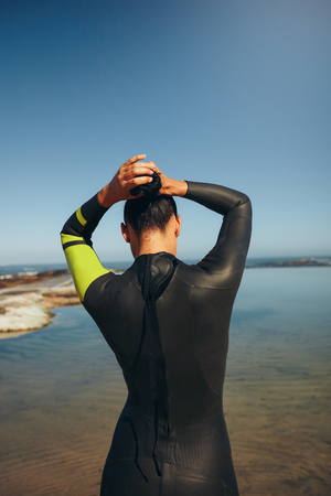 triathlon: Rear view of young triathlete on the lake preparing for a race wearing a wetsuit. Female triathlon athlete tying her hair and getting ready for the competition.