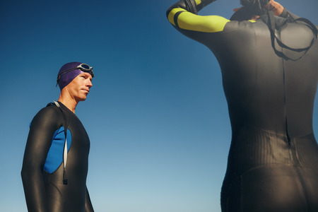 wetsuit: Outdoor shot of a determined male triathlete wearing wetsuit ready for triathlon competition with a female. Athletic swimmer standing with his swimming gear on against sky.