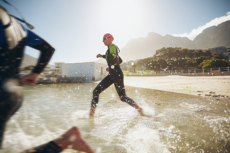 swimming suit: Participants running into the water for start of a triathlon. Two triathletes rushing into water. Stock Photo