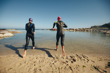 sportsperson: Rear view of participants wearing wetsuits running into the water for start of a triathlon race. Triathletes practicing for triathlon competition. Stock Photo