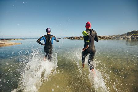 Twee sportieve zwemmers die het water met hun wetsuits op. Concurrenten in natte pakken lopen in het water bij de start van een triatlon. Stockfoto