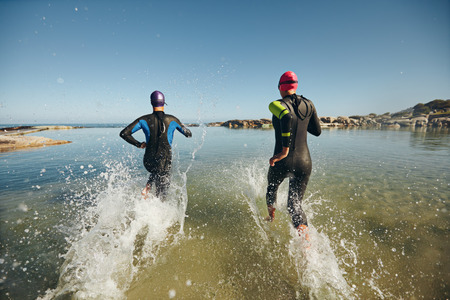 swimming suit: Two athletic swimmers entering the water with their wetsuits on.  Competitors in wet suits running into the water at the start of a triathlon.