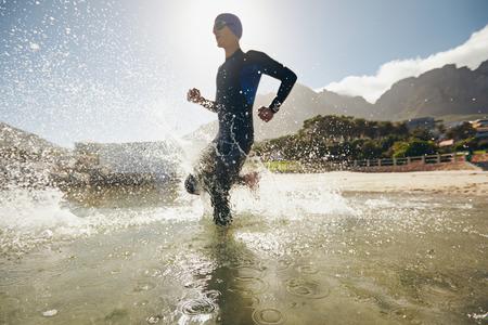 男性トライアスリートに水を実行しています。湖のトライアスロン競技のトレーニング。