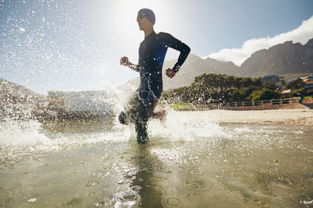 triathlon: Male triathlete running into water. Training for triathlon competition in lake. Stock Photo