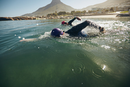 hombre deportista: Nadadores del Triathlon batiendo el agua. Los atletas que practican para la carrera triathletic en el lago.