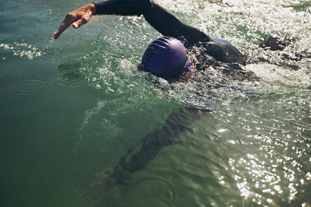 swimming race: Male swimmer swimming in open water. Athlete practicing for the competition. Stock Photo
