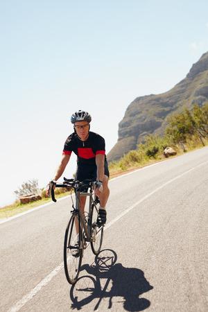 田舎道の下の乗車男性サイクリストのショット。トライアスロン自転車でサイクリングします。