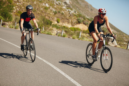 road cycling: Woman competing in the cycling leg of a triathlon with male competitor. Triathletes riding bicycle on open road.