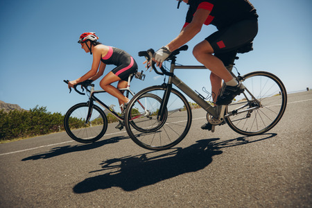 road cycling: Action shot of a racing cyclists. Cyclist riding bicycles down hill on country road. Practicing for competition. Stock Photo