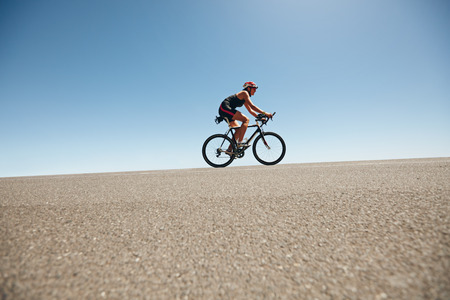 extreme angle: Female cyclist on a country road training for triathlon. Young woman riding bicycle up hill.