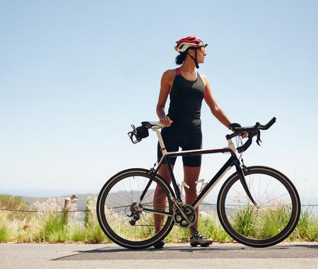 Volledige lengte beeld van jonge vrouwelijke fietser op zoek weg. Fit jonge vrouw, gekleed in sportkleding staande met haar fiets.