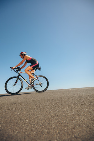 Image of female cyclist riding bicycle down hill. Athlete training for cycling event of a triathlon competition.