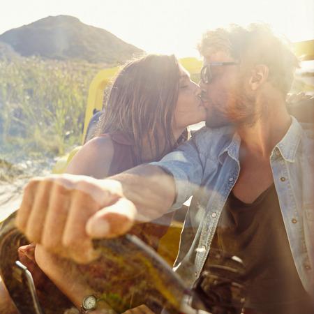 personas besandose: Joven pareja bes�ndose en el coche. Pareja de enamorados en viaje por carretera que se divierten. Foto de archivo
