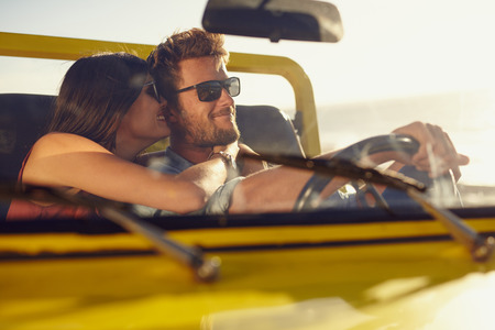 Romantic young couple sharing a special moment while on a road trip. Man driving car with girlfriend.