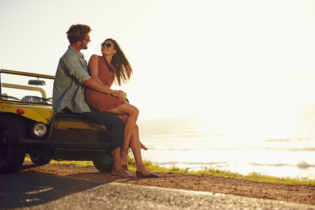 Young couple looking into each others eyes. Romantic young couple sitting on hood of their car enjoying the moment, outdoors with copy space. Young couple in love on a road trip.