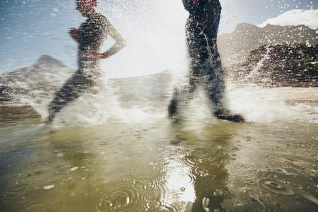 Image of splashes of water while triathletes running in lake.  Athletes training for triathlon race.