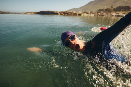 オープンウォーター スイミングします。男性アスリートは湖で泳ぐ。トライアスロン長距離水泳。