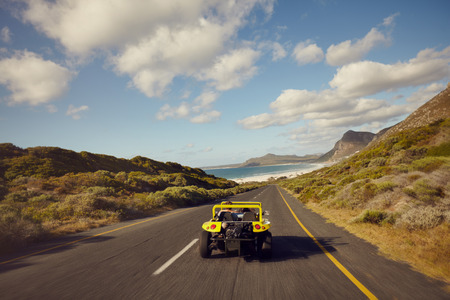 Rear view of couple driving in small beach buggy car on open road. Young man and young woman on road trip on a beautiful summers day.