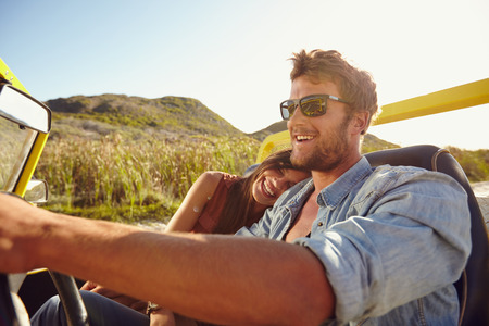 open topped: Happy young couple going on holidays together in a buggy car. Loving couple enjoying on a road trip.