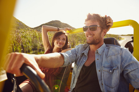 Woman looking at man driving buggy car on a summer day. Loving young couple on road trip.