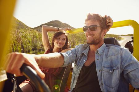 Vrouw op zoek naar man rijden buggy auto op een zomerse dag. Liefdevolle jong koppel op road trip.