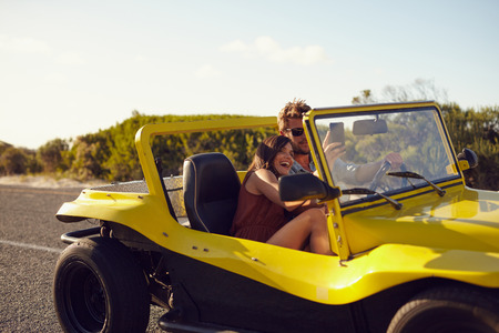 open topped: Young happy couple enjoying road trip in their beach buggy car with woman taking a selfie from her mobile phone.