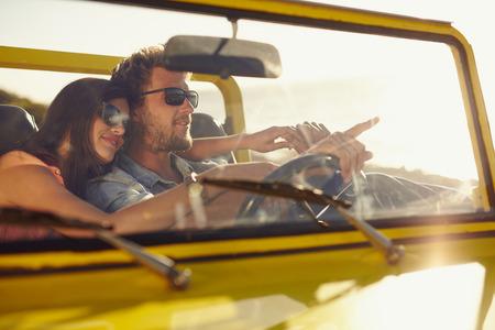 hombre manejando: Hombre joven que conducía el auto señala algo interesante a su novia. Caucásica pareja de vacaciones de verano, Pareja romántica en viaje por carretera. Foto de archivo