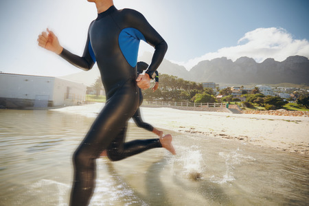 triathlon: Image of two triathletes rushing into the water. Athlete running into the water, training for a triathlon.