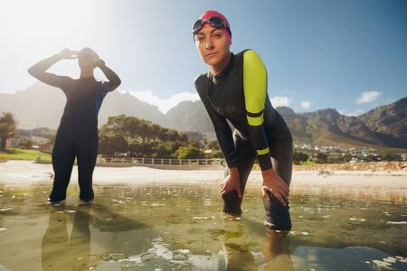 wet suit: Confident young woman in wet suit standing in water looking at camera. Young triathletes preparing for competition. Triathlon training at the lake. Stock Photo