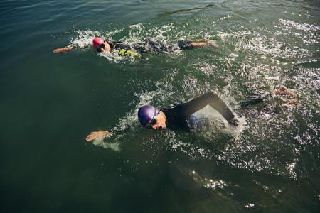 competencia: Los competidores que luchan en el evento de nataci�n de un triatl�n.