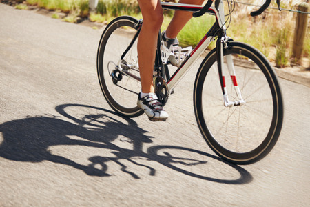 Low section image of woman riding bicycle on country road. Cropped image of female athlete cycling. Action shot of a racing cyclist. Foto de archivo