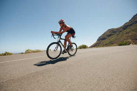 triathlon: Image of young woman cycling on the country road. Fit female athlete riding down hill on bicycle. Woman doing cycling training.