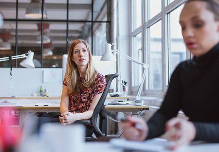 women thinking: Imagen de la mujer joven que se sienta en su escritorio mirando a otro lado pensando. Ejecutivo de sexo femenino en la oficina perdida en sus pensamientos.