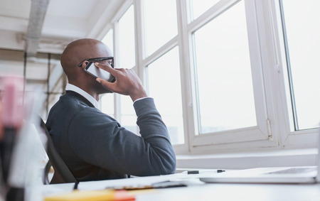 african business man: Young african man sitting at his desk talking on his mobile phone in office. African executive using cell phone while at work.