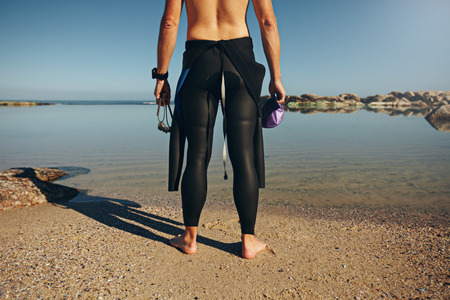 Rear view of young man standing on lake wearing wetsuit. Cropped shot of a triathlete preparing for a race wearing a wetsuit prior to the swim start.