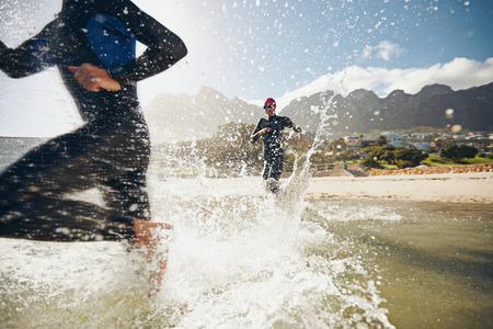 triathlon: Image of triathletes rushing into the water. Athlete running into the water, training for a triathlon.