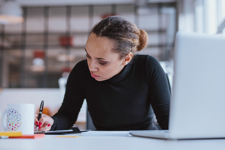 creative writing: Portrait of young woman working at her desk. Busy african woman taking notes.