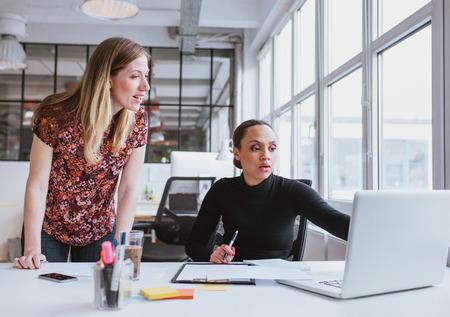 ejecutivo en oficina: Mujeres ejecutivas que trabajan juntos en nuevo proyecto. Equipo creativo usando la computadora port�til para obtener informaci�n en el cargo. Foto de archivo