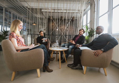 Diverse team of business people sitting in office lobby discussing new business ideas.