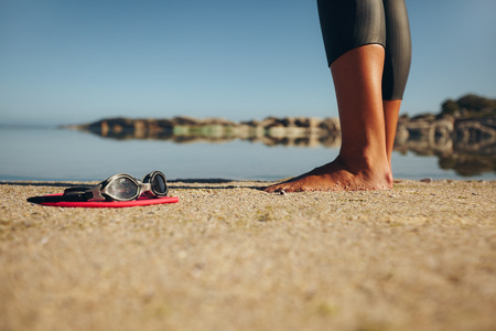 swimming suit: Swim goggles on the sand with feet of a woman standing by. Focus on goggles. Stock Photo