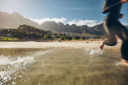 participant: Triathlon participant running in the water. Triathlete preparing for competition.