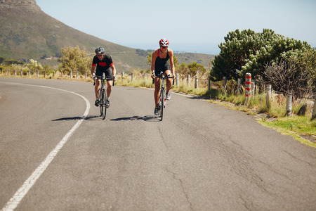 cycling mountain: Cyclist riding bikes on open road. Triathletes cycling on bicycles. Practicing for triathlon race.