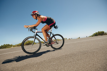 triathlon: Female cyclist on a country road training for competition. Young woman riding bicycle down hill.