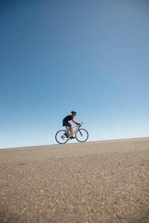 Image of male cyclist riding bicycle up hill. Athlete training for cycling event of a triathlon competition.