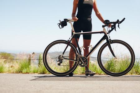 彼女は自転車で立っている女性アスリートのセクション低ショット。田舎道で彼女の自転車を持つ女性サイクリスト。彼女の周期を持つ女性トライ