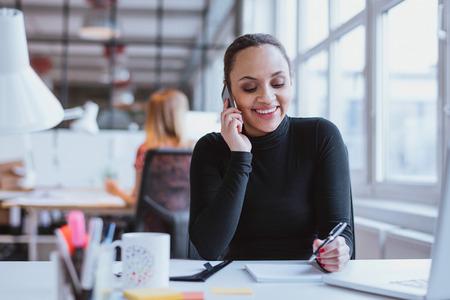 personen: Gelukkige jonge vrouw zit op haar bureau werken en een telefoontje beantwoorden.