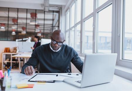 ejecutivo en oficina: Ejecutivo joven sentado en su escritorio con la computadora portátil que lee un documento. Hombre africano que trabaja en oficina.