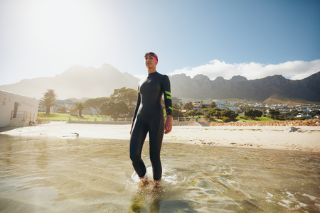 Image of fit young female triathlete walking into the sea wearing wetsuit. Triathlete in training at the beach.