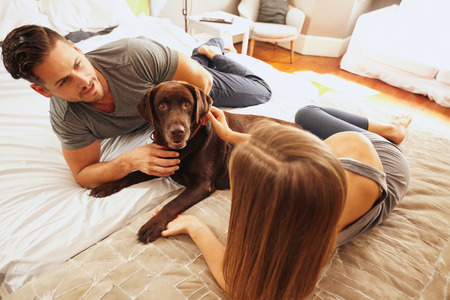 Shot of young couple on bed with pet dog. Family relaxing on bed having a casual chat. Archivio Fotografico